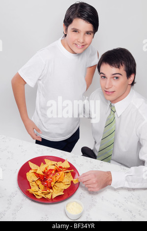 Portrait of a man and his son eating nachos with salsa - Stock Photo