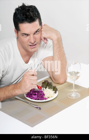 Man frowning over a salad - Stock Photo