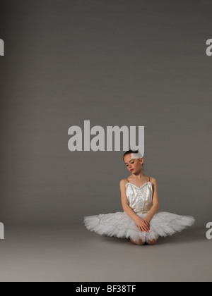 Girl in white tutu kneeling. - Stock Photo