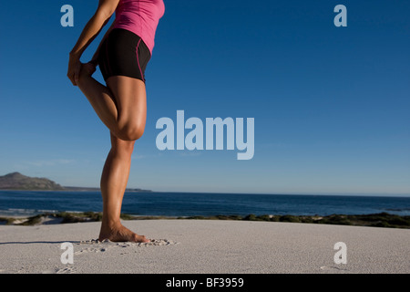 Young Woman barefoot stretches leg - Stock Photo