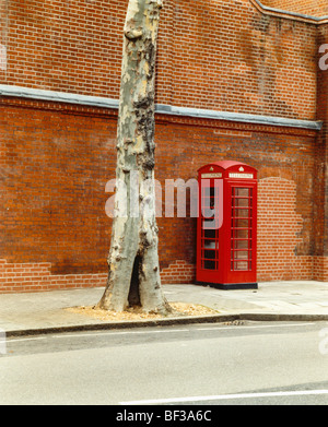 Traditional red phone box in street - Stock Photo
