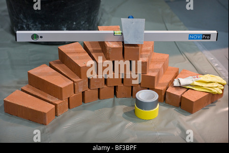 Water level and brick trowel on building bricks - Stock Photo