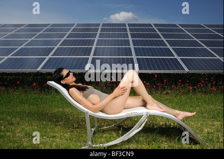 woman sunbathing in front of solar panel - Stock Photo