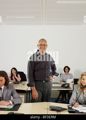 A man stands with a group of office workers - Stock Photo
