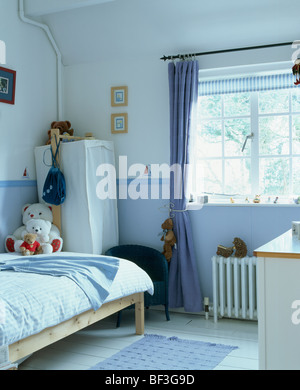Blue curtain at window in child's bedroom with blue wallpaper dado and tent-wardrobe in corner of the room - Stock Photo