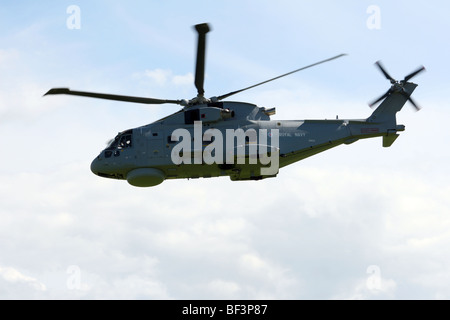 The UK Royal Navy Merlin medium lift helicopter is a variant of the EH101 helicopter developed by AgustaWestland. - Stock Photo