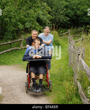 Disabled boy being pushed along by loving parents. - Stock Photo