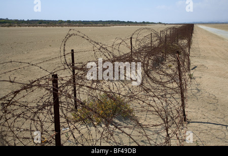 rusty barbed wire fence on the akrotiri salt flats the limit of the western Sovereign Base Area SBA in the republic - Stock Photo