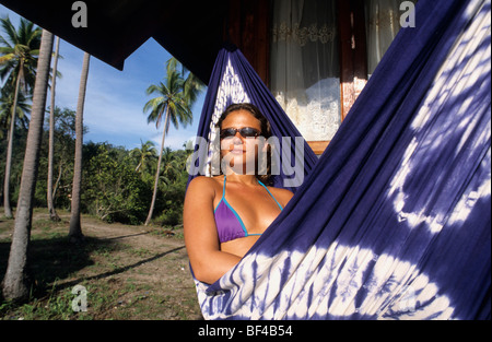 Young woman in a hammock under palm trees in front of a hut in the bay of Tong Nai Pan, Koh Pha Ngan Island, Thailand, - Stock Photo