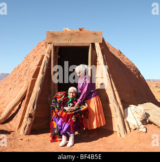 Navajo Family of 2 Women Outdoors in Front of Family Hogan - Stock Photo