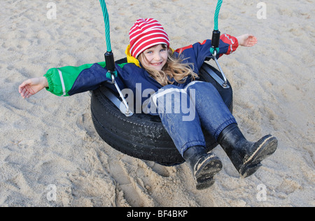 Little girl, 7 years, sitting in a tire swing - Stock Photo