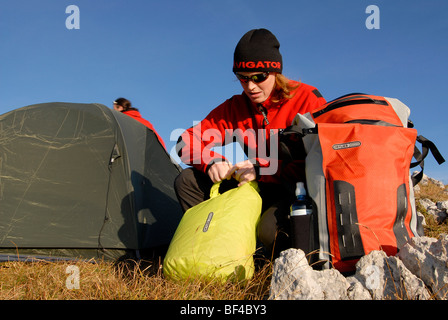 Hikers, young man and woman buildig a bivouac with tent, sleeping bag, backpack and sleeping pad, Mt. Heidachstellwand, - Stock Photo