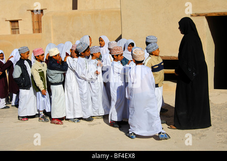 Teacher with a mixed classroom of lively boys and girls on a school field trip at the Fort of Nizwa, Sultanate of - Stock Photo