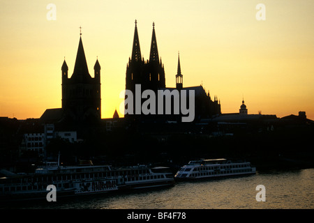 Gross St. Martin church and the Koelner Dom Cologne Cathedral in backlight, sunset over the old town, Cologne, North - Stock Photo