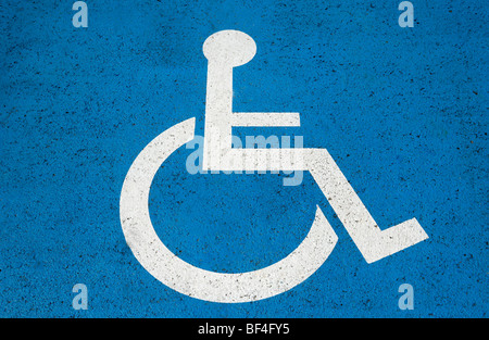 Sign for disabled parking on a blue background - Stock Photo