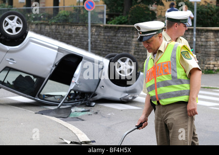 Daihatsu car having rolled over in a traffic accident, lying on its roof, police officer writing up the accident, - Stock Photo