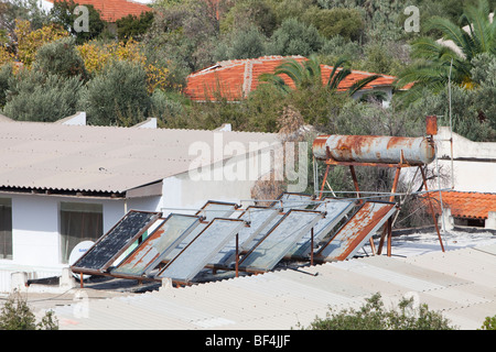 Solar water heating panels on the roof of a launderette in Teos, Western Turkey. - Stock Photo