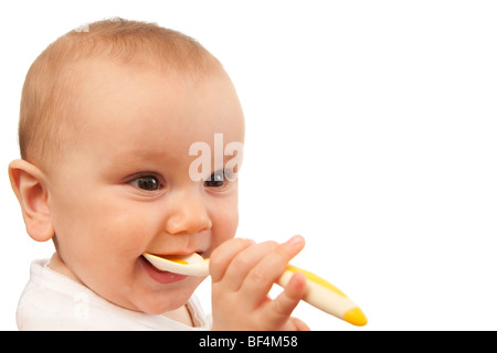 Baby putting spoon in his mouth. Isolated. - Stock Photo