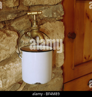 Close-up of brass tap and white enamel pot on stone wall - Stock Photo