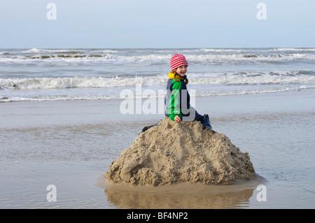 Little girl sitting on a pile of sand on the North Sea beach, Vejer beach, Jutland, Denmark, Europe - Stock Photo