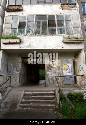 Neglected apartment building exterior with window boxes and plants growing in windows, Ekaterinburg Russia - Stock Photo