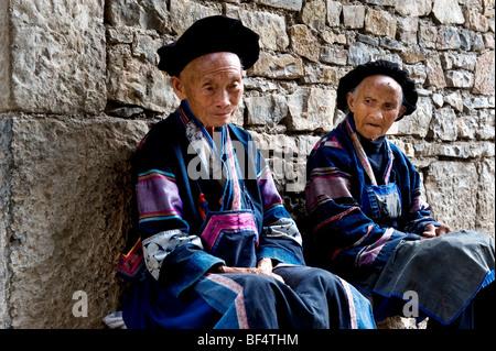 Two Miao women sitting together, Rongjiang County, Qiandongnan Miao and Dong Autonomous Prefecture, Guizhou Province, - Stock Photo