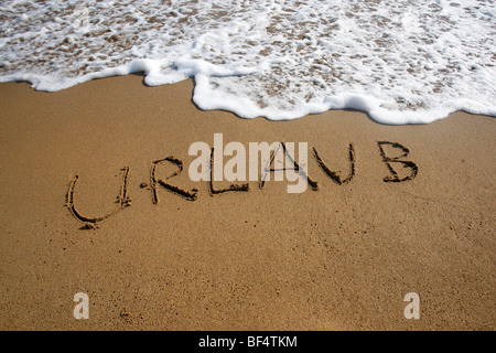 Urlaub, German for Holiday, written in the sand on a beach, Corfu, Greece, Europe - Stock Photo