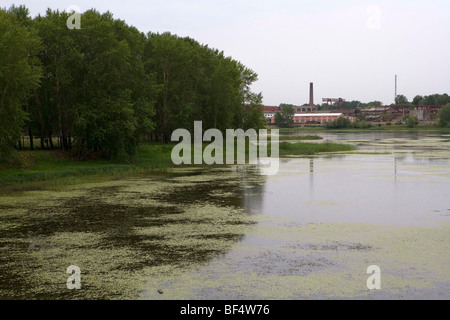 Polluted river with algae growth and industrial buildings in background, Urals, Russia - Stock Photo