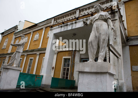 Worker statues at entrance of old soviet civic building in rural Russia - Stock Photo