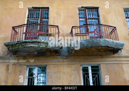 Russian apartment building with metalwork hammer and sickle symbols on balconies, architectural detail - Stock Photo
