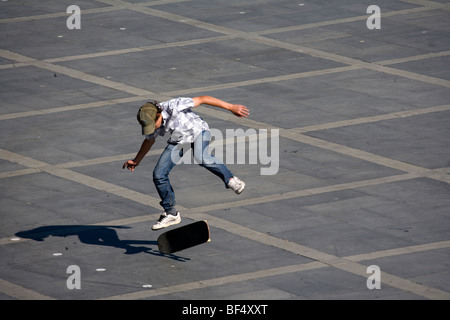 Skateboarder doing skateboarding trick in town square, Ekaterinburg, Russia - Stock Photo