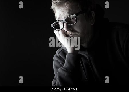 Low Key Shot of a Geek Looking Upset - Stock Photo