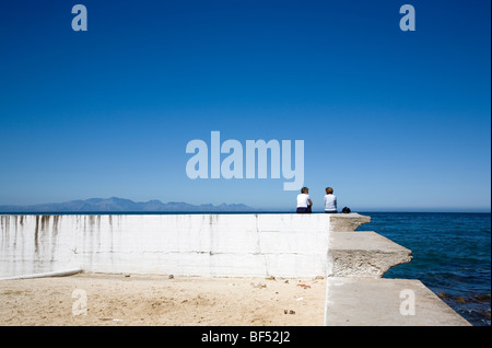 Two women chatting on Sea wall - Stock Photo