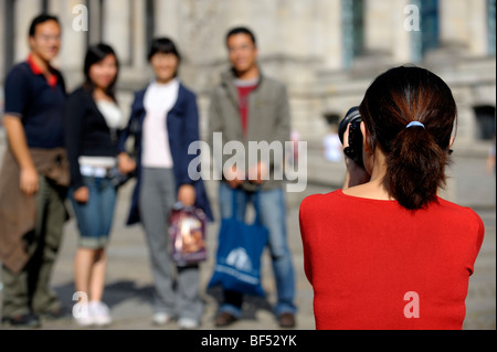 Asian photographer taking a photograph of a group of tourists, Berlin, Germany, Europe - Stock Photo