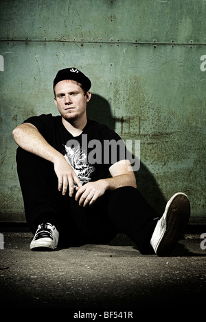 Portrait of a young man wearing a black cap sitting in front of a old steel door, youth, looking directly at the - Stock Photo