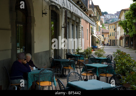 Old couple talk and drink coffee in a bar in Barga Tuscany - Stock Photo