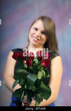 Studio, UK, Britain. Portrait of a young woman smiling and holding a bunch of red roses - Stock Photo