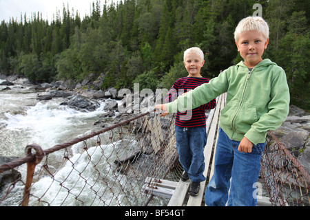 Two young boys on a suspension bridge - Stock Photo