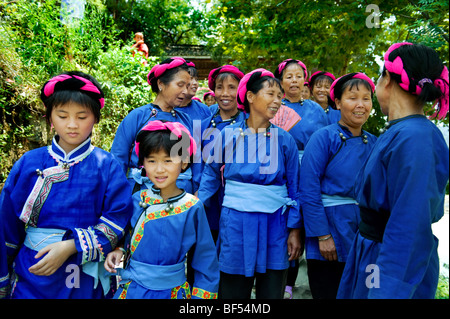 Dong women in traditional costume walking together, Zhaoxing Dong Village, Liping County, Guizhou Province, China - Stock Photo