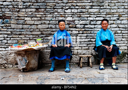 Two elderly Dong street vendors in traditional costume sitting, Zhaoxing Dong Village, Liping County, Guizhou Province, - Stock Photo