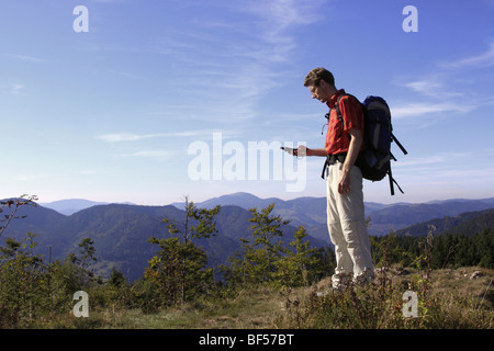Geocacher checking the coordinates with a GPS navigation system on Mt. Leder Tschobenstein in Bernau in the Black - Stock Photo