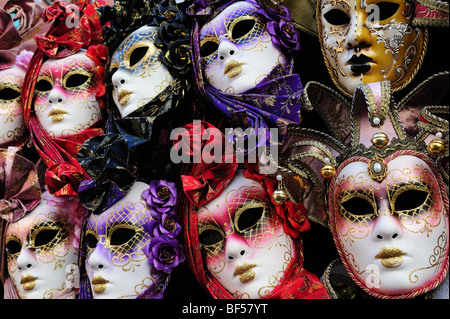 Row of Venetian face masks on display for sale at a stall in a Venice market - Stock Photo
