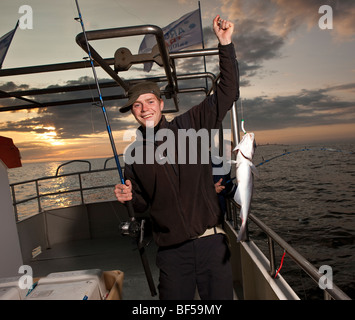 Teenager with cod, North Atlantic, Raufarhofn, Iceland - Stock Photo
