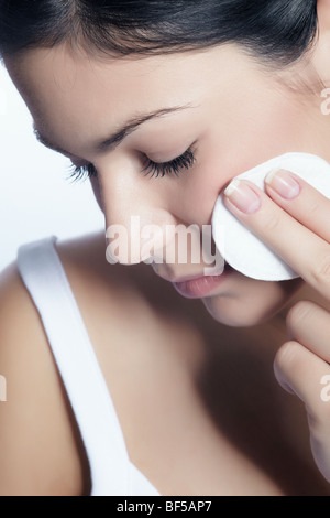 Young woman using a cotton pad for cleansing, beauty - Stock Photo