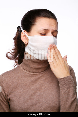 Coughing woman in a medical mask on a white background - Stock Photo