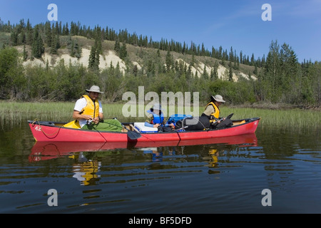 Family with young boy in a canoe, fishing, Teslin River, high cut bank behind, Yukon Territory, Canada - Stock Photo