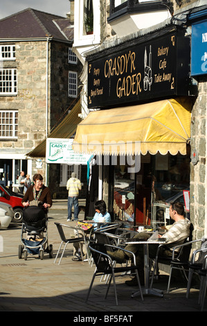 People sitting at tables outside cafe in Dolgellau town centre , Gwynedd, Snowdonia National Park, Wales UK - Stock Photo