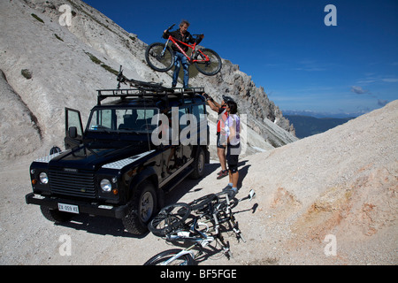 Mountain bike riders loading bicycles off a Landrover at the Kreuzjoch mountain gorge, Fodara Vedla basin, Parco - Stock Photo
