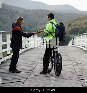 A cyclist paying the toll-keeper to cross the old wooden privately owned toll bridge at Penmaenpool, Mawddach river - Stock Photo