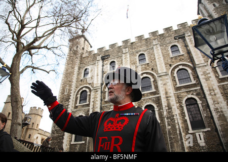 A Beefeater tells the tales of the Tower of London to visiting tourists. - Stock Photo